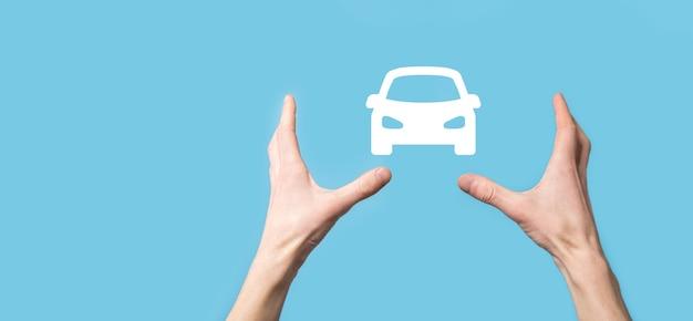 青い背景に車の自動アイコンを表示する男性の手。