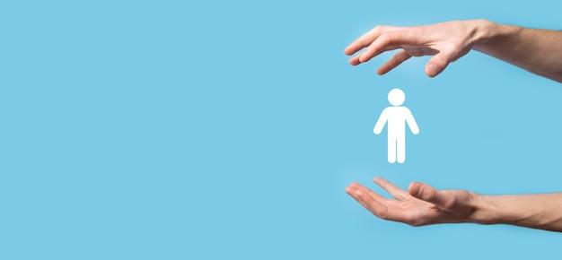 青い背景に人間のアイコンを表示する男性の手。
