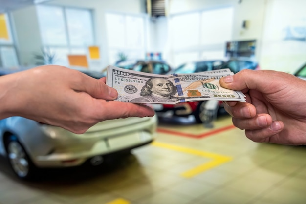 Male hand dollar, take money on car background. business concept