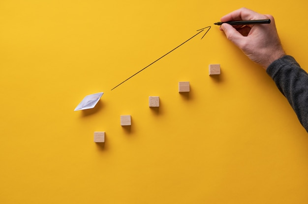 Male hand drawing an arrow pointing upwards in front of an origami made paper boat.