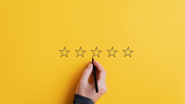 Мужская рука рисует пять звезд подряд