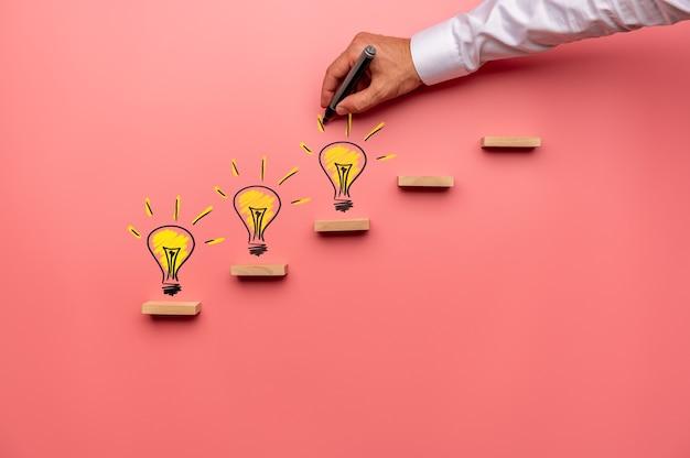 概念的なイメージの木製の階段に黄色の電球を描く男性の手。ピンクの背景の上。