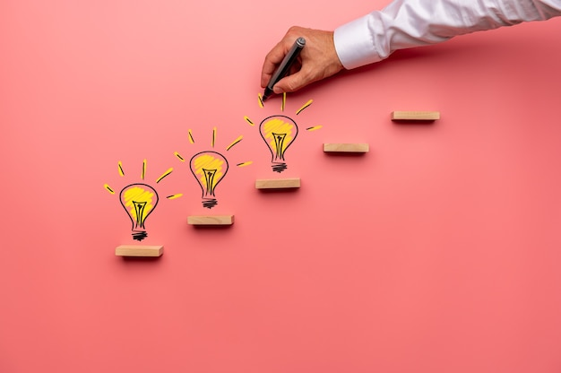 Male hand drawing yellow light bulbs on wooden steps in a conceptual image. over pink background.