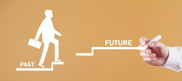 Male hand draws human symbol climb past to future stairs.