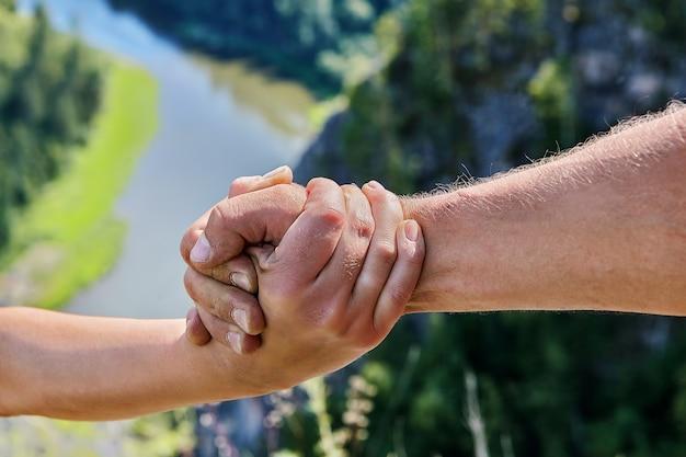 Male hand embraces female hand against  backdrop of  natural landscape.