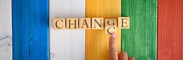 남자 손은 글자가 있는 나무 큐브를 뒤집고 개념적 이미지에서 chance in을 change로 변경합니다. 화려한 나무 배경 위에.