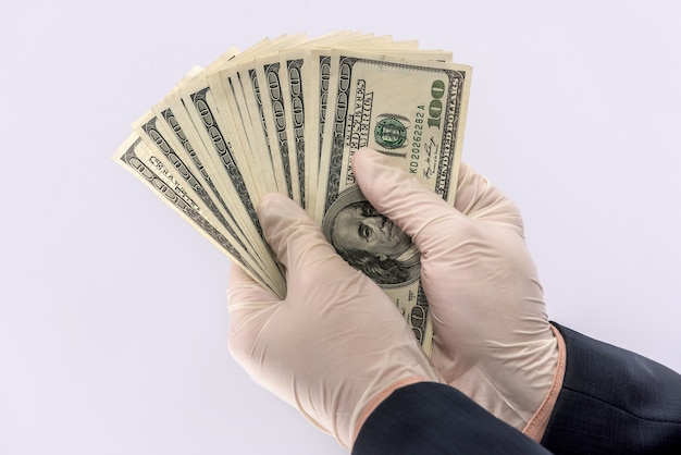 Male hand give dollar to pay in protective gloves  for safety isolated on white background. medical concept covid 19 coronavirus