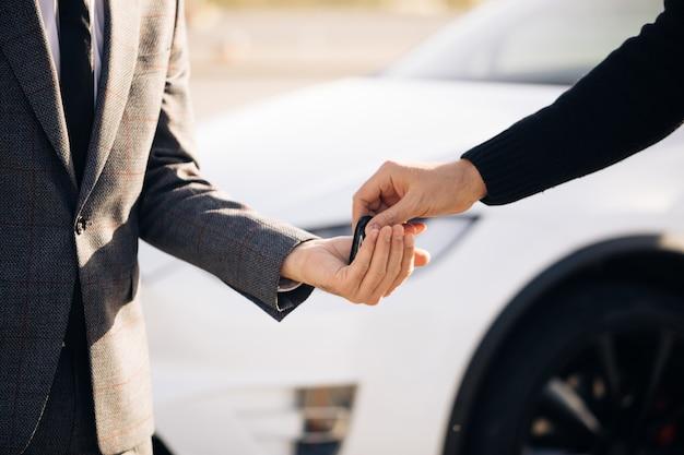 男性の手は、自動車販売店のクローズアップで男性の手に車のキーを与えます
