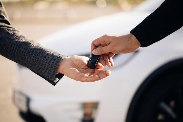 Мужская рука дает ключи от машины мужской руке в автосалоне крупным планом