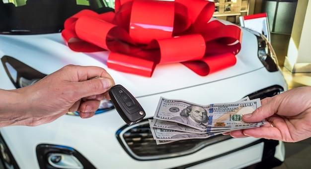 남성 손은 돈을주고 자동차 키, 새 차를 배경으로 가져갑니다. 재원
