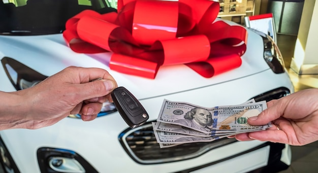 Male hand gives money and take car keys, new car as background. finance