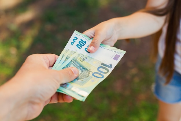 男性の手は子供、100ユーロ紙幣にお金を与える