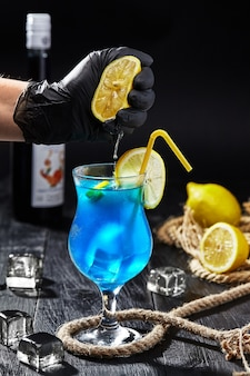 Male hand in glove squeezing lemon into glass with blue lagoon cocktail