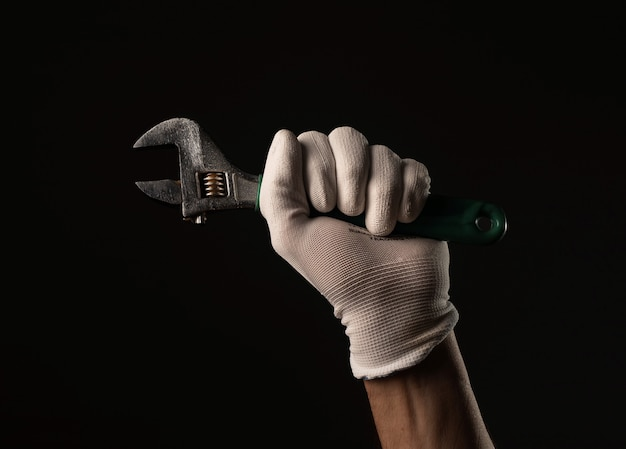 Male hand in gloves holding wrench tool close up over black background.