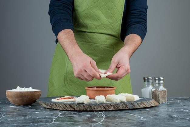 Mano maschio in guanti che producono cibo sul tavolo di marmo.