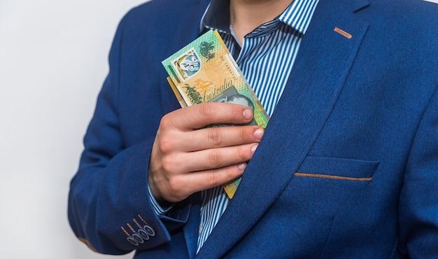 호주 달러 지폐를 주머니에 숨기는 남성 손