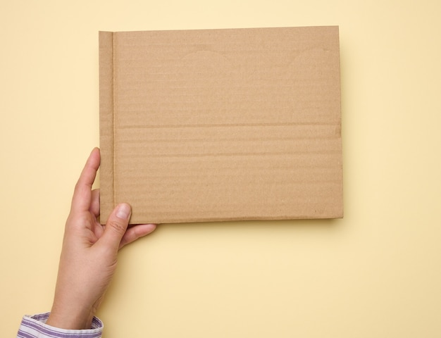 Male hand hold a blank torn piece of brown paper, beige background