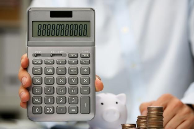 Мужская рука держит калькулятор в руке дома