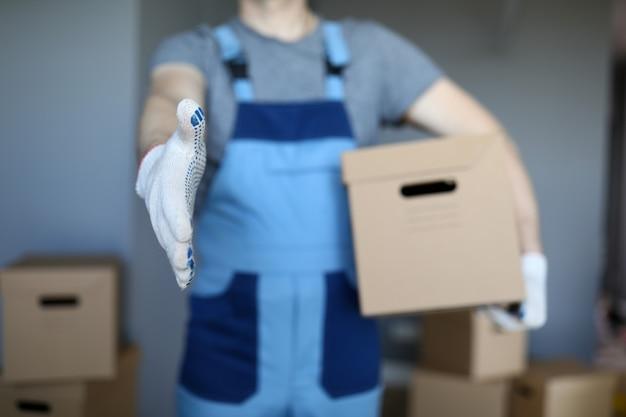 Male hand hold cardboard against new flat closeup