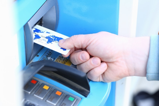 Male hand hold credit card aganist atm