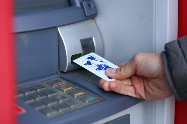 Мужской рукой держите кредитную карту аганист банкомат