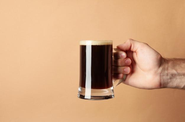 Мужская рука держит стакан пива на коричневом фоне
