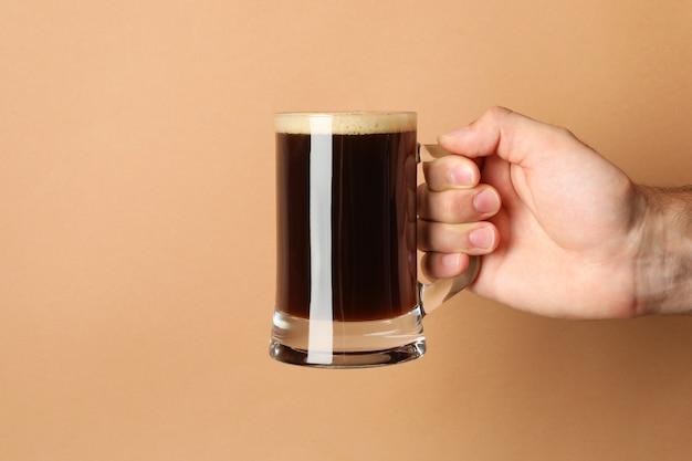 男性の手は茶色のビールのグラスを保持します。