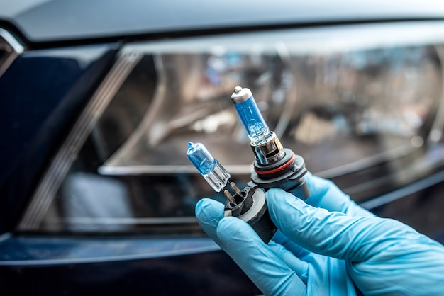 Male hand hold a halogen light bulb against of the headlights, all for repair car