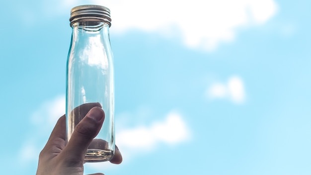 Male hand hold transparent glass bottle. empty bottle fill with blue sky. against blue sky. empty copy space. clean air environment nature for life concept idea background