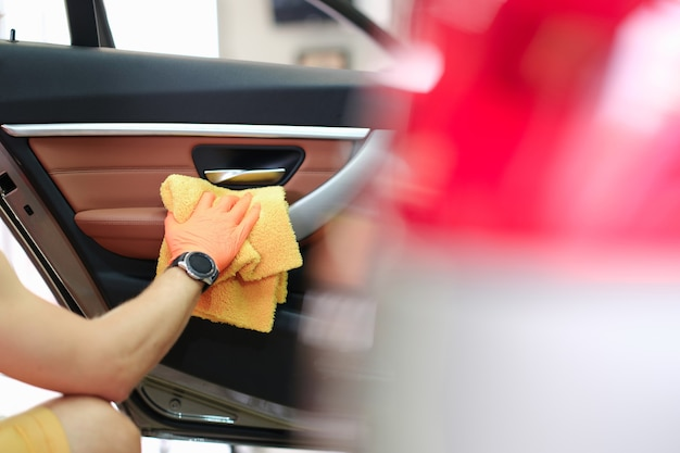 Male hand hold yellow microfiber towel and wipes the door with leather panel closeup