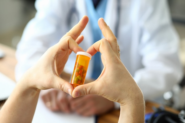 Male hand hold yellow pill jar in hospital doctor office.