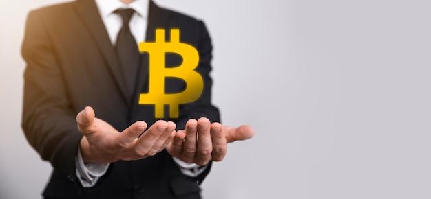 파란색 배경에 비트코인 아이콘을 들고 있는 남성 손. bitcoin cryptocurrency 디지털 비트 코인 btc 통화 기술 비즈니스 인터넷 개념입니다.