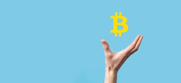 Мужская рука держит значок биткойн на синем фоне. биткойн криптовалюта цифровая битовая монета btc технология валюты бизнес интернет-концепция.