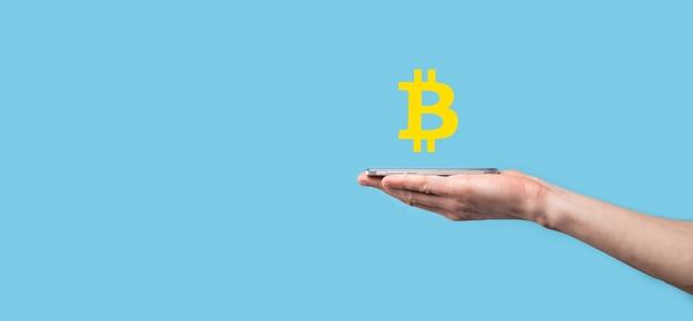 青い背景にビットコインアイコンを持っている男性の手。ビットコイン暗号通貨デジタルビットコインbtc通貨テクノロジービジネスインターネットコンセプト。