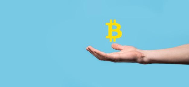 青の背景にビットコインのアイコンを持っている男性の手。 bitcoin cryptocurrency デジタル ビット コイン btc 通貨テクノロジー ビジネス インターネット コンセプト。
