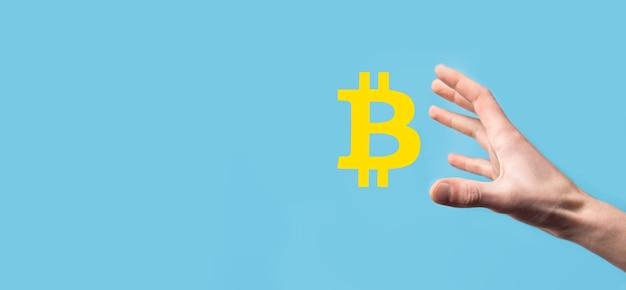 파란색 배경에 bitcoin 아이콘을 들고 남자 손. bitcoin cryptocurrency 디지털 비트 코인 btc 통화 기술 비즈니스 인터넷 개념.