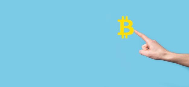 青い表面にビットコインアイコンを持っている男性の手