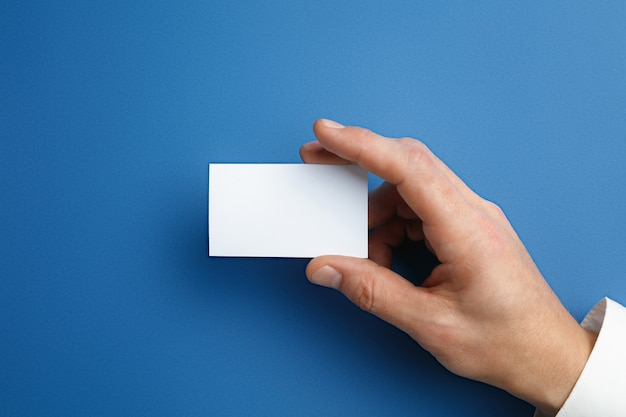 テキストまたはデザインの青い壁に空白の名刺を持っている男性の手。連絡先またはビジネスで使用するための空白のクレジットカードテンプレート。財務、オフィス。コピースペース。