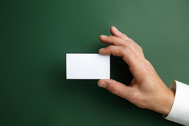 テキストまたはデザインの緑の壁に空白の名刺を持っている男性の手。連絡先またはビジネスで使用するための空白のクレジットカードテンプレート。財務、オフィス。コピースペース。