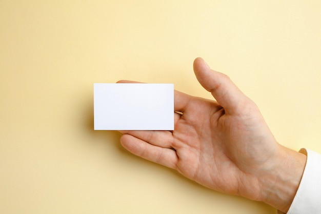 텍스트 또는 디자인에 대 한 부드러운 노란색 벽에 빈 명함을 들고 남자 손. 연락처 또는 비즈니스 사용을위한 빈 신용 카드 템플릿. 금융, 사무실. copyspace.