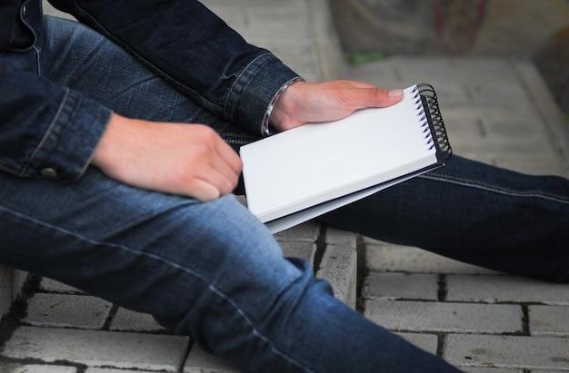 本を持って外に座っている男性の手