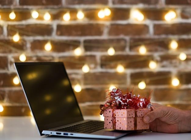 노트북 컴퓨터에 크리스마스 선물을 들고 남성 손. 즐거운 성탄절 보내시고 새해 복 많이 받으세요. 조명된 벽돌 벽 배경