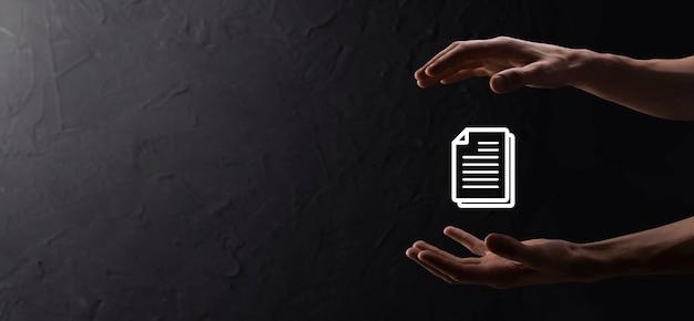 Мужская рука, держащая значок документа на синем фоне. концепция технологии интернет бизнеса системы данных управления документами. система управления корпоративными данными dms