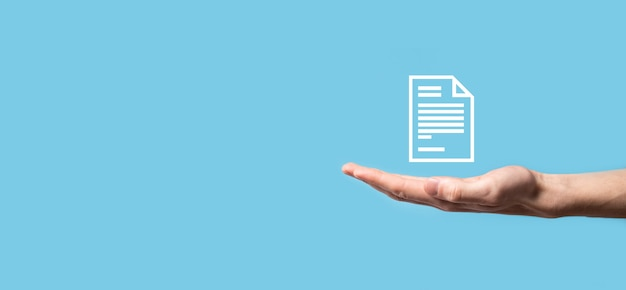 Мужская рука, держащая значок документа на синем фоне. концепция технологии интернет бизнеса системы данных управления документами. система управления корпоративными данными dms.