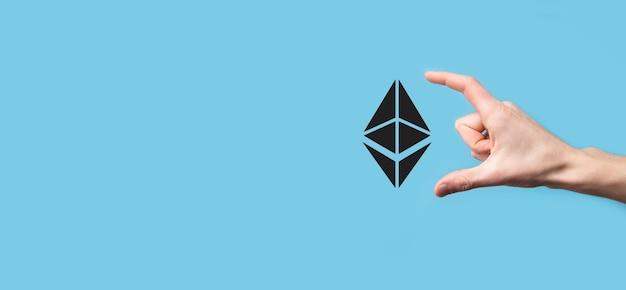青い背景にイーサリアムアイコンを持っている男性の手。イーサリアムと暗号通貨の投資コンセプト。ブロックチェーンテクノロジーの交換、取引、譲渡、投資。