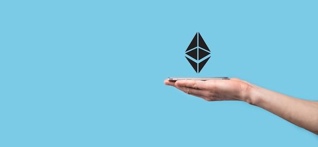 青の背景にイーサリアムのアイコンを持っている男性の手。イーサリアムと暗号通貨投資のコンセプト。ブロックチェーン技術の交換、取引、移転、投資。