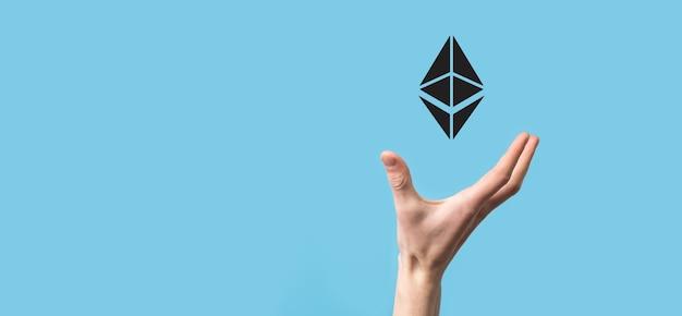 青い背景にイーサリアムのシンボルを持っている男性の手。イーサリアムと暗号通貨の投資コンセプト。ブロックチェーンテクノロジーの交換、取引、譲渡、投資。