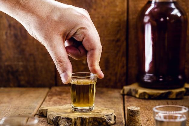 ブラジルで「ピンガ」または「カシャーサ」と呼ばれる蒸留酒のグラスを持っている男性の手、アランビックの風景