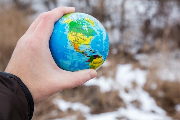 惑星の地球の地球を持っている男性の手。