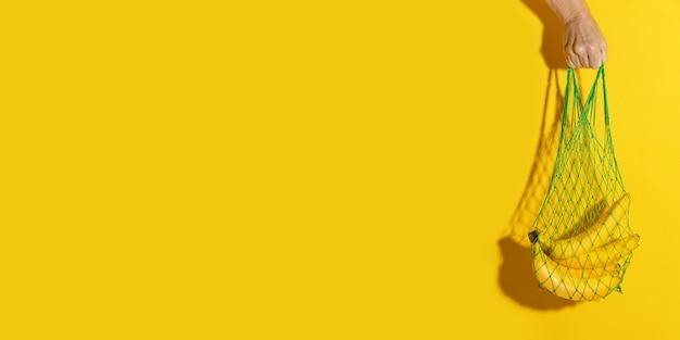コピースペースと黄色の壁にバナナと緑のメッシュバッグを持っている男性の手。ゼロウェイストショッピングコンセプト。バナナのストリングショッピングバッグ。プラスチックの拒絶。
